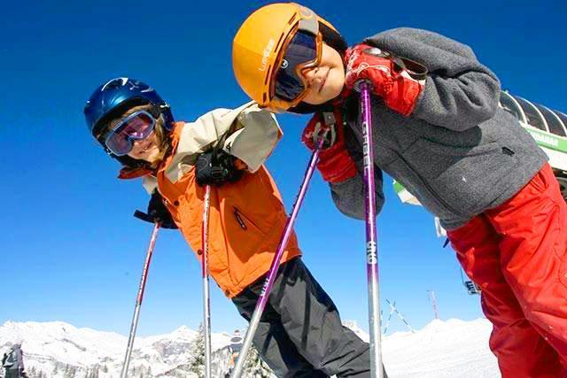Des enfants sourient à l'appareil photo pendant la pause au milieu de leur cours de ski pour enfants (6-17 ans) - Midi - Intermédiaire qvec l'école de ski Evolution 2 Chamonix.