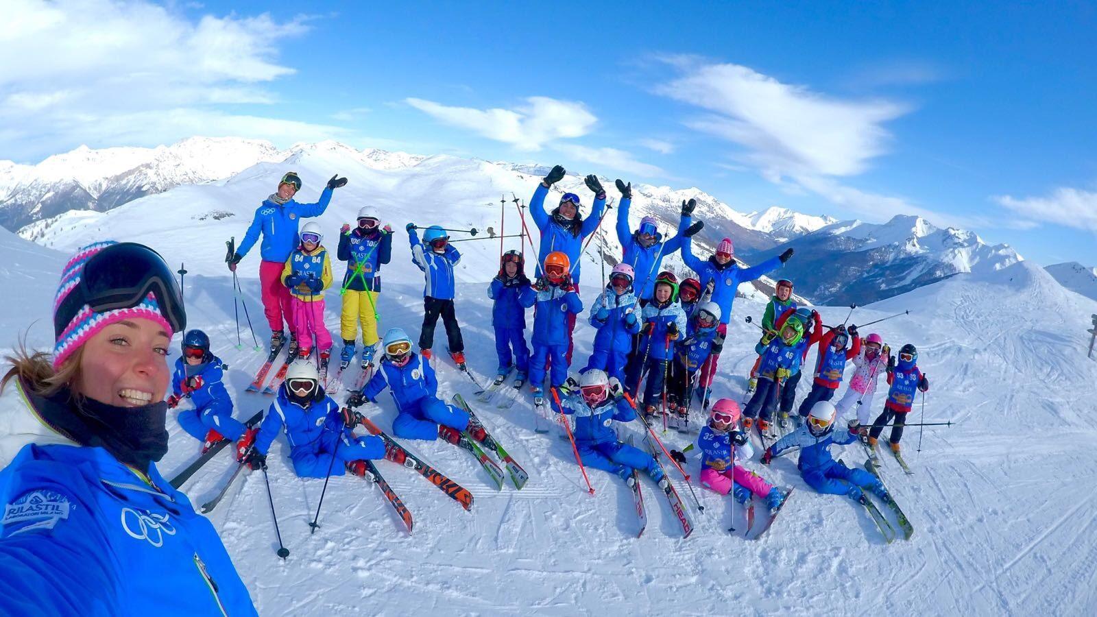 Un gruppo di bambini in posa con il maestro di sci della Scuola di Sci Olimpionica sulla cima di una montagna a Sestriere prima di iniziare le Lezioni sci bambini (5-14 anni) - Festività - Con esperienza.