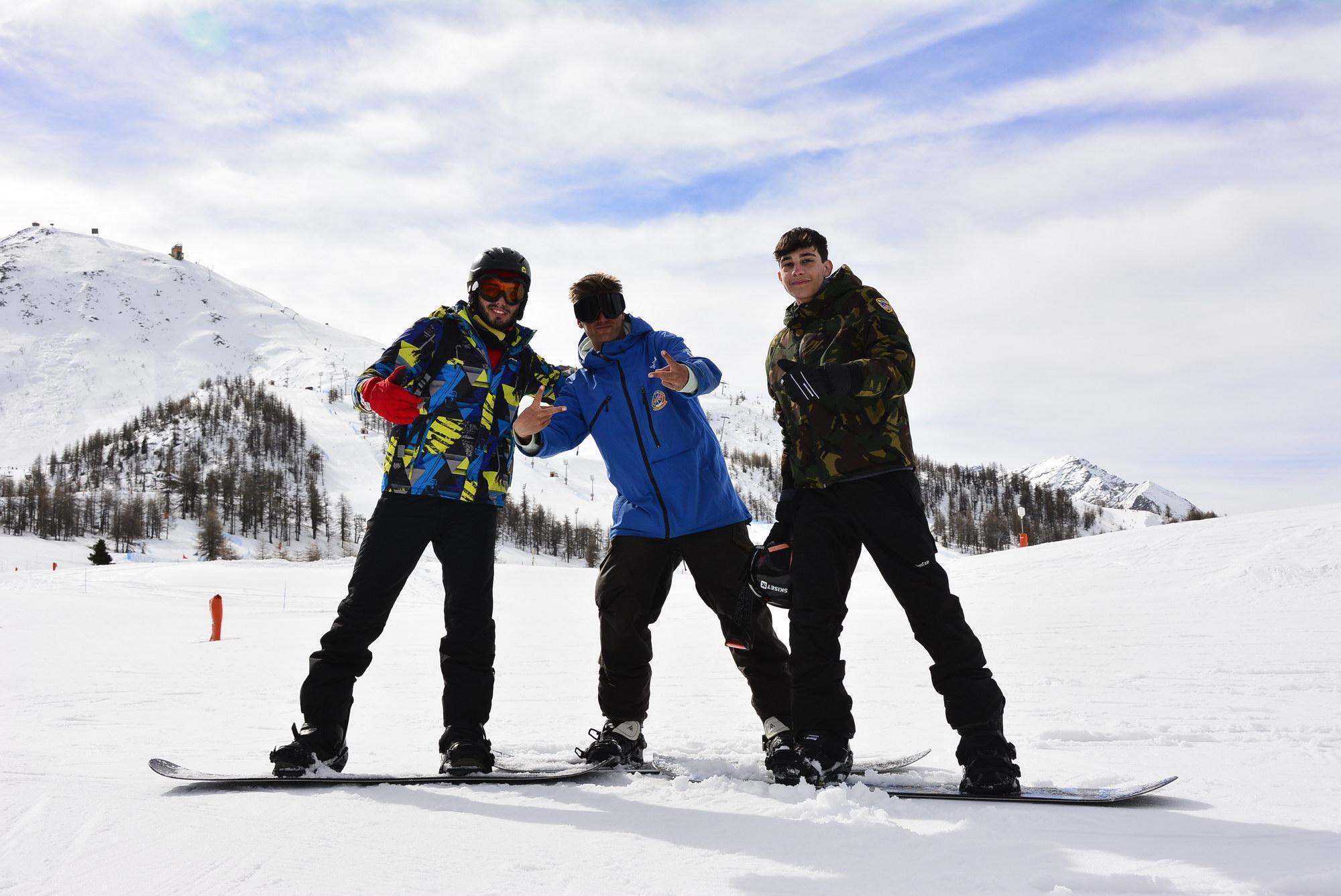 Un gruppo di amici divertendosi durante una delle Lezioni di snowboard per bambini e adulti - Tutti i livelli organizzate dalla Scuola di Sci Olimpionica nel comprensorio sciistico della Via Lattea a Sestriere.