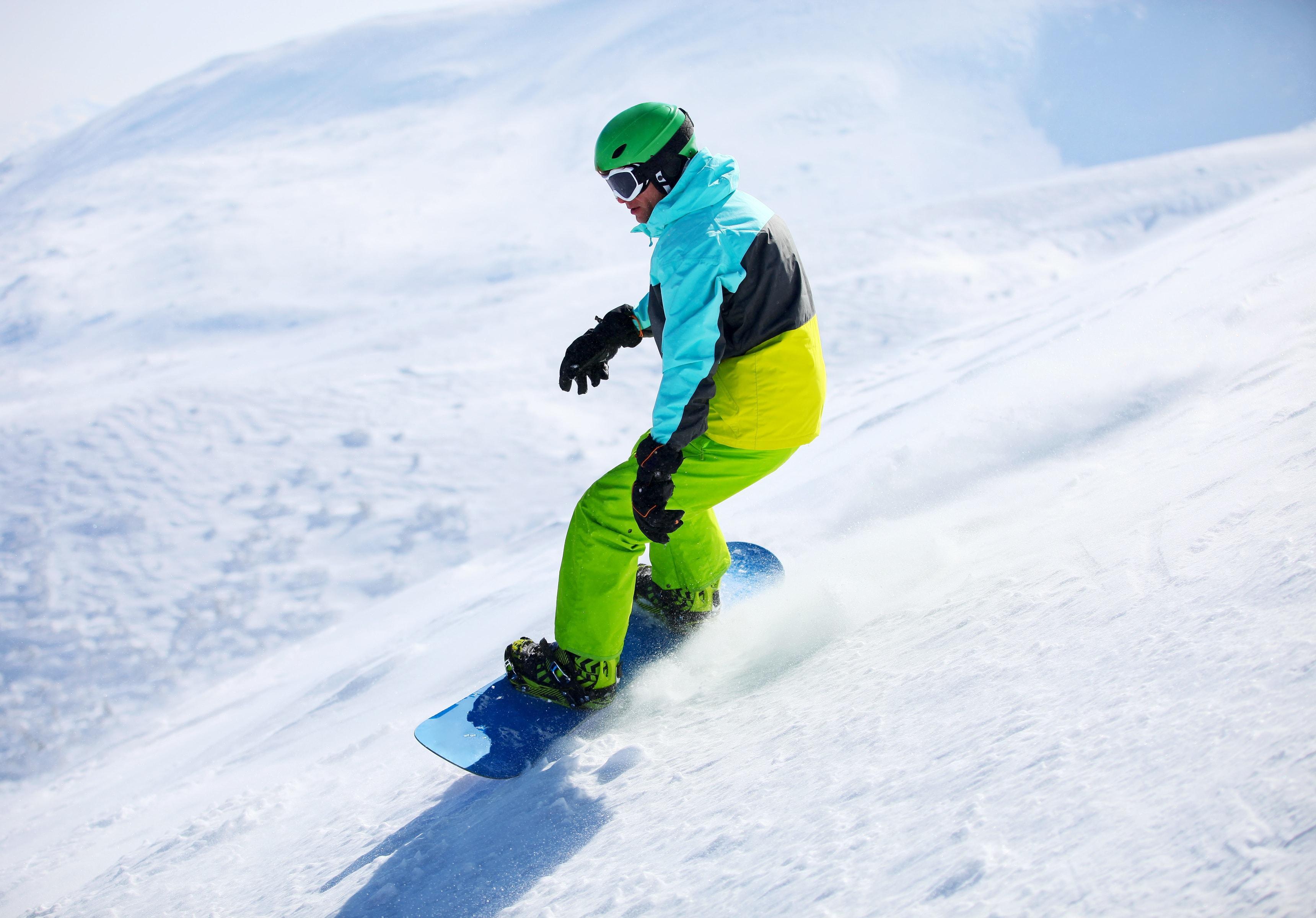 Uno snowboarder sta scendendo una pista a Sestriere durante una delle Lezioni di snowboard per bambini e adulti - Festività organizzate dalla Scuola di Sci Olimpionica.