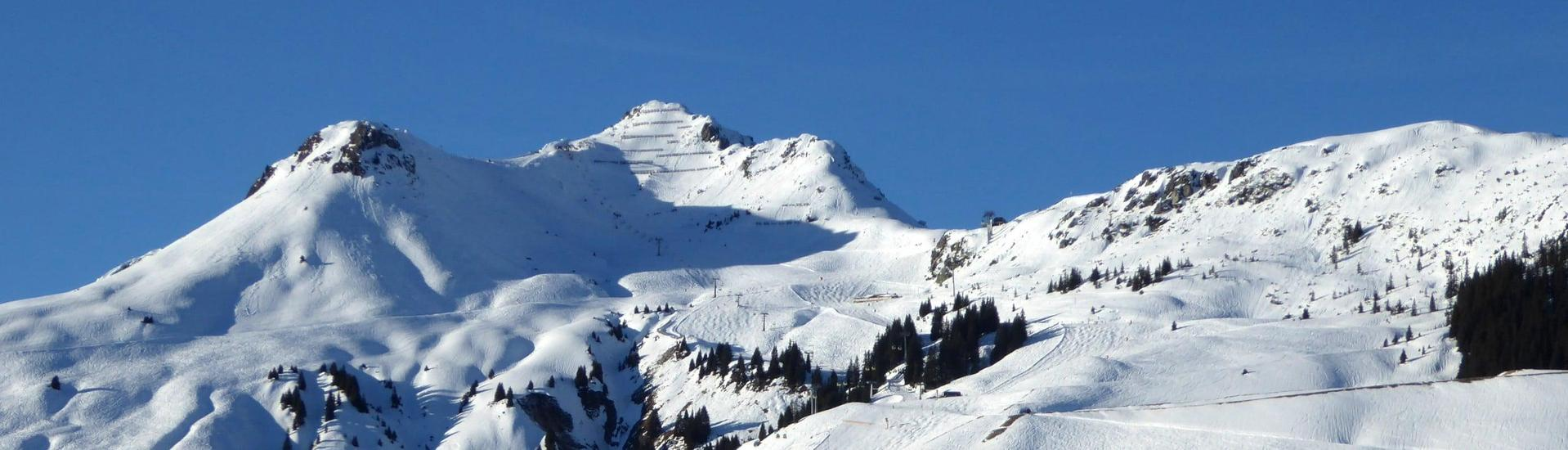 View over the sunny mountain landscape while learning to ski with the ski schools in Fieberbrunn.