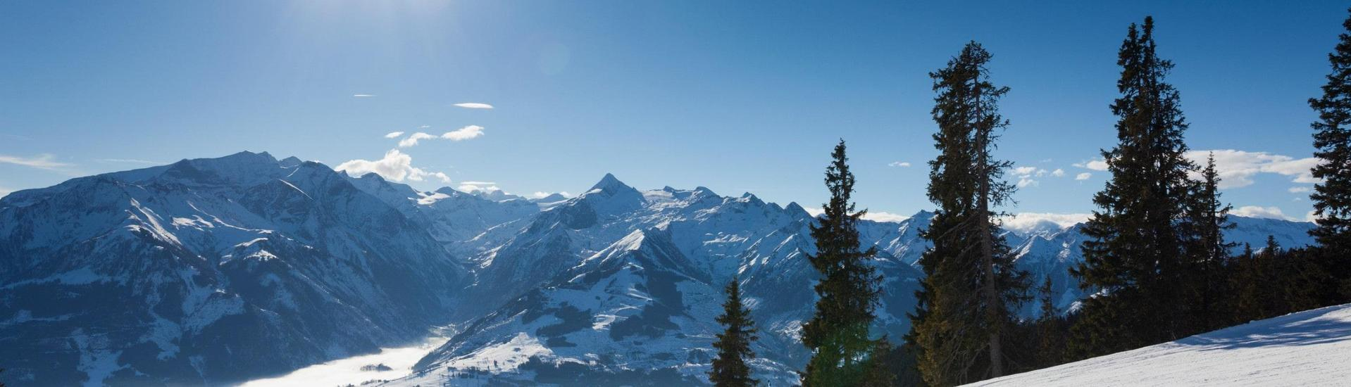 View over the sunny mountain landscape while learning to ski with the ski schools in Kaprun.